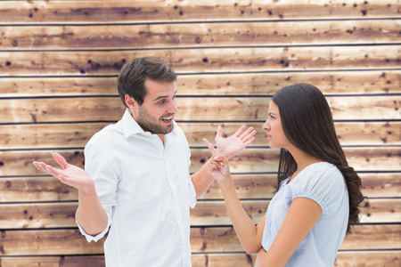 accusing: Angry brunette accusing her boyfriend against wooden planks background Stock Photo