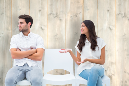 pleading: Brunette pleading with angry boyfriend against pale wooden planks