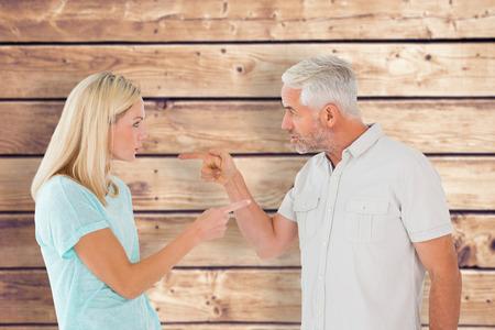 argument: Unhappy couple having an argument  against wooden planks background