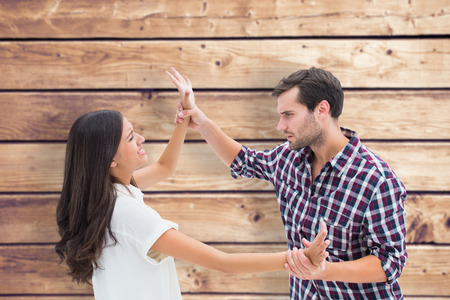 overpowered: Fearful brunette being overpowered by boyfriend against wooden planks background