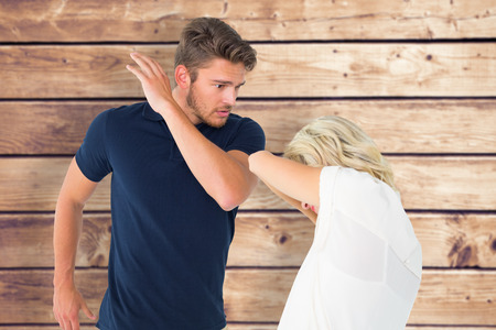 cowering: Angry man about to hit his girlfriend against wooden planks background Stock Photo