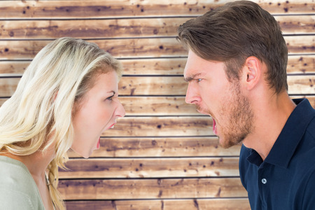 strife: Angry couple shouting during argument against wooden planks background Stock Photo