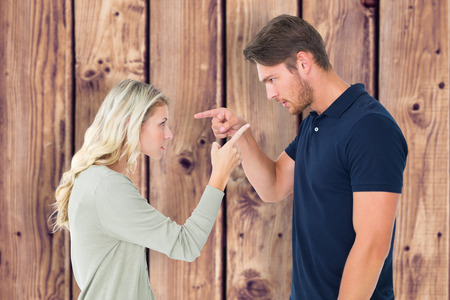 argument: Angry couple facing off during argument against wooden planks background