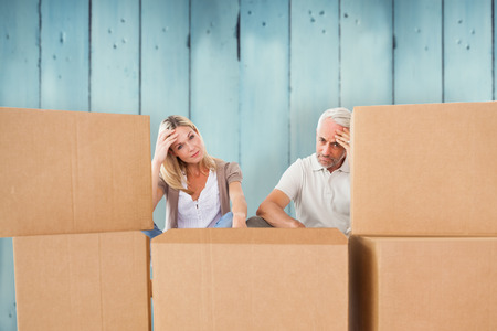 moving: Stressed couple looking at moving boxes against wooden planks