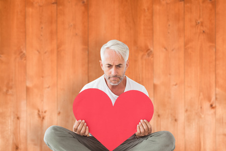 gloominess: Upset man sitting holding heart shape against wooden planks