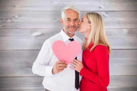 man arm: Handsome man holding paper heart getting a kiss from wife against wooden planks background
