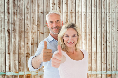 thumbs up: Smiling couple showing thumbs up together against faded pine wooden planks