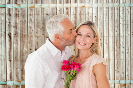 pale wood: Affectionate man kissing his wife on the cheek with roses against wooden background in pale wood