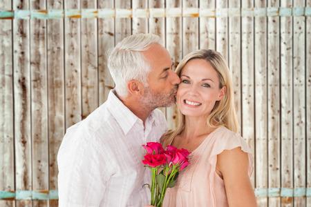 parejas romanticas: Hombre cari�oso que besa a su esposa en la mejilla con rosas sobre fondo de madera de madera clara