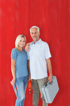 Happy couple holding DIY tools against red wooden planks photo
