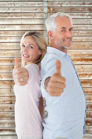 pale wood: Smiling couple showing thumbs up together against wooden background in pale wood