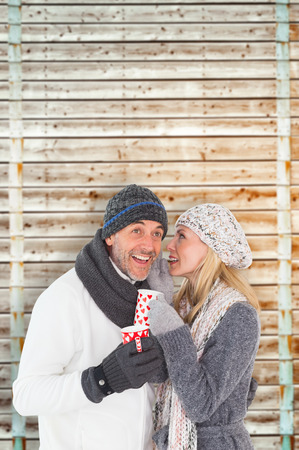 pale wood: Happy couple in winter fashion holding mugs against wooden background in pale wood Stock Photo
