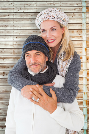 faded: Happy couple in winter fashion embracing against faded pine wooden planks