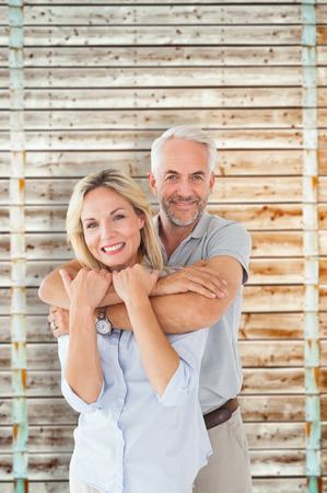 pale wood: Happy couple standing and hugging against wooden background in pale wood Stock Photo