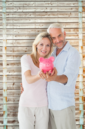 pale wood: Happy couple showing their piggy bank against wooden background in pale wood