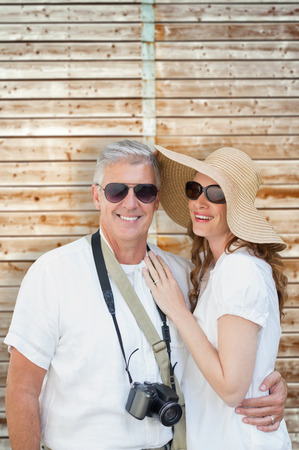 pale wood: Vacationing couple against wooden background in pale wood Stock Photo