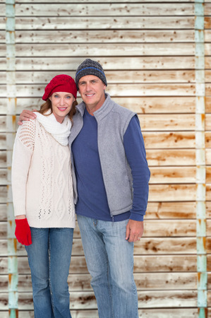 pale wood: Happy couple in warm clothing against wooden background in pale wood