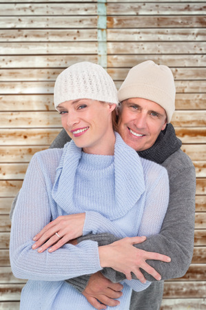 pale wood: Casual couple in warm clothing against wooden background in pale wood Stock Photo