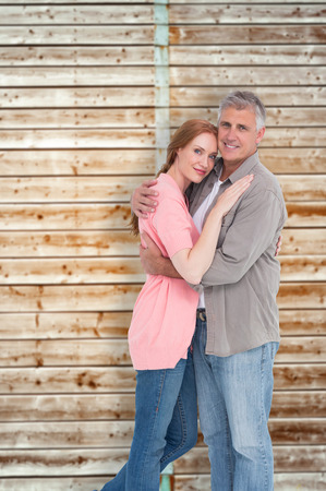 pale wood: Casual couple hugging and smiling against wooden background in pale wood