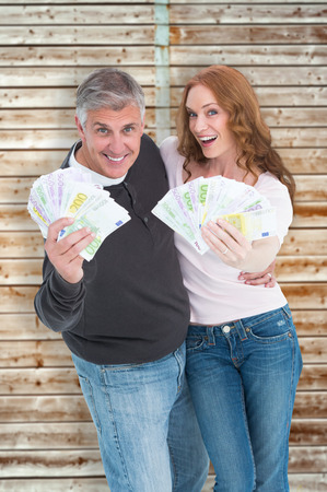 pale wood: Casual couple showing their cash against wooden background in pale wood