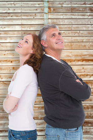 pale wood: Casual couple smiling and looking up against wooden background in pale wood