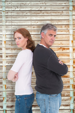 pale wood: Casual couple not speaking after fight against wooden background in pale wood