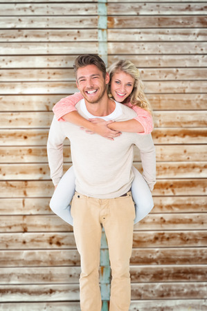 pale wood: Handsome man giving piggy back to his girlfriend against wooden background in pale wood