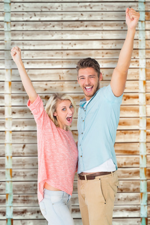 pale wood: Attractive couple smiling and cheering against wooden background in pale wood Stock Photo