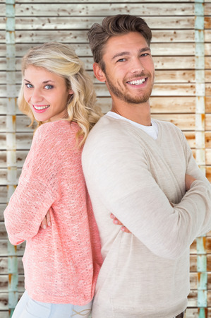 pale wood: Attractive couple smiling with arms crossed against wooden background in pale wood