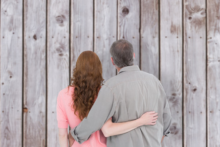 arm around: Casual couple standing arm around against wooden planks