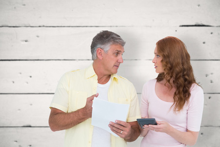 figuring: Casual couples working out their bills against white wood Stock Photo