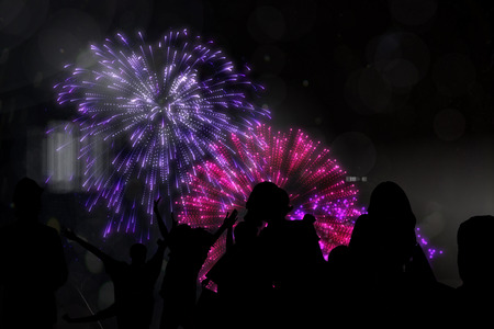 incidental people: Silhouette of cheering people against colourful fireworks exploding on black background