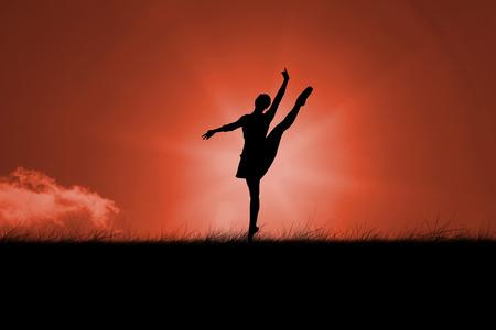 silueta bailarina: Silueta de la bailarina contra el cielo rojo sobre la hierba
