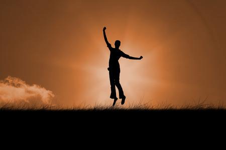 euphoria: Silhouette of jumping woman against sunrise Stock Photo