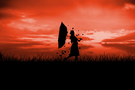incidental people: Silhouette of woman holding broken umbrella with leaves blowing against red sky over grass