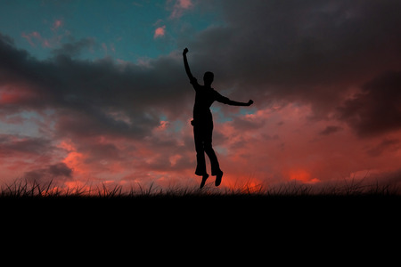 red sky: Silhouette of jumping woman against red sky over grass Stock Photo