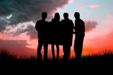 red sky: Silhouette of team holding a poster against red sky over grass Stock Photo