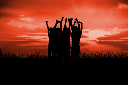 incidental people: Silhouette of cheering people against red sky over grass Stock Photo
