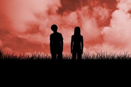 red sky: Silhouette of two children against red sky over grass Stock Photo