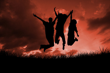 incidental people: Silhouette of people jumping against red sky over grass