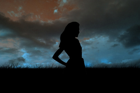 incidental people: Silhouette of slim woman against blue sky over grass