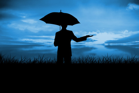 incidental people: Silhouette of businessman holding umbrella against blue sky over grass