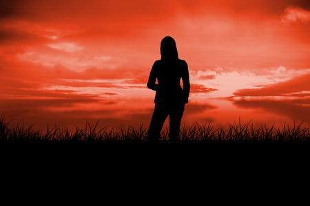 red sky: Silhouette of businesswoman standing against red sky over grass