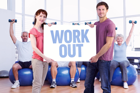 Couple holding a white sign against work out