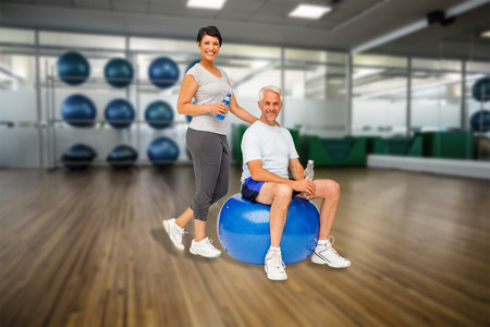 Full length portrait of a happy fit couple against large empty fitness studio with shelf of exercise balls photo