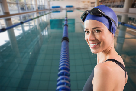 swimming goggles: Fit swimmer standing by the pool smiling at camera against empty swimming pool with lane markers Stock Photo