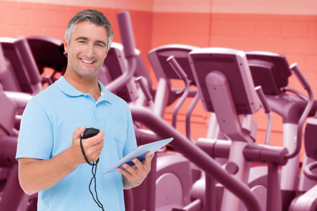 Trainer smiling at the camera against close up of treadmills in a fitness centre Imagens