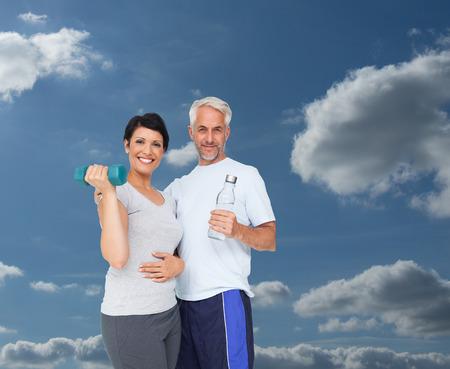 mujeres maduras: Pareja ajuste feliz con mancuernas y botella de agua contra el cielo y las nubes