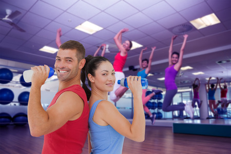 zumba: Composite image of fit man and woman smiling at camera together