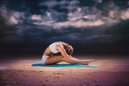 Gorgeous fit blonde in seated forward bend pose  against dark cloudy sky photo